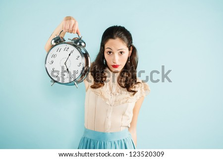 portrait of a young woman holding a huge clock. funny concept. - stock photo