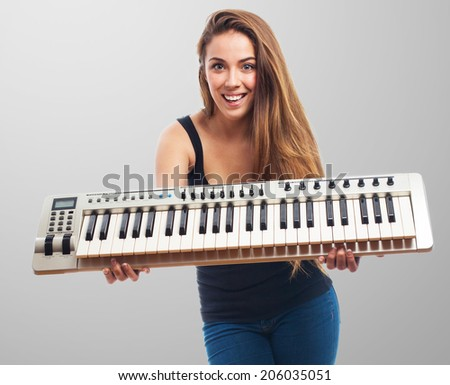 portrait of a young woman holding a piano - stock photo