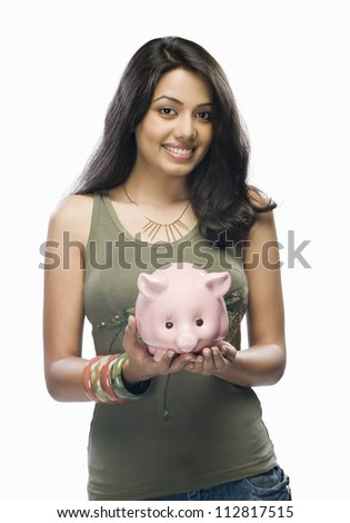Portrait of a young woman holding a piggy bank - stock photo