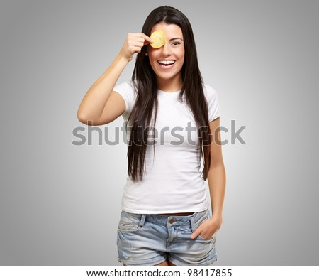 portrait of a young woman holding a potato chip in front of her eye over a grey background - stock photo