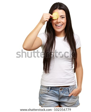 portrait of a young woman holding a potato chip in front of her eye over a white background - stock photo