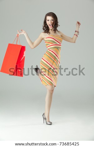portrait of a young woman holding a red shopping bag in one hand, jumping on one foot, laughing and looking very happy. - stock photo