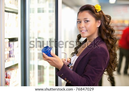 Portrait of a young woman holding container in front of refrigerator in the supermarket - stock photo