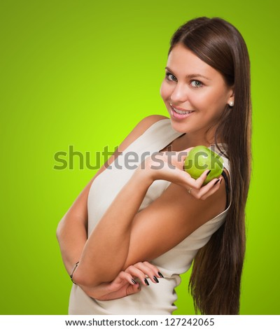 Portrait Of A Young Woman Holding Green Apple against a green background - stock photo