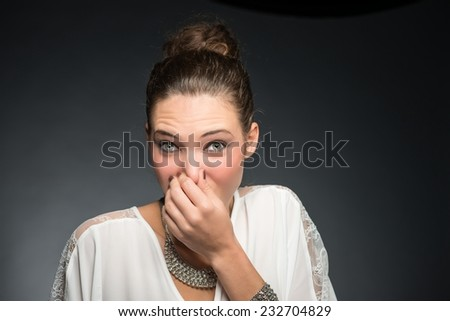 Portrait of a young woman holding her nose because of a bad smell. Isolated against gray background. - stock photo