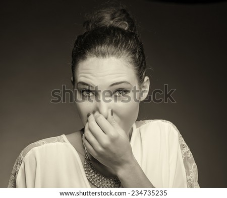 Portrait of a young woman holding her nose because of a bad smell. Isolated against gray background.