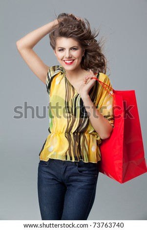 portrait of a young woman holding in one hand a red shopping bag and the other one in her hair. she is laughing and looking very happy. - stock photo