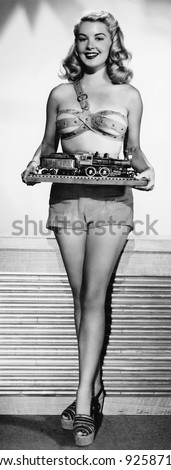 Portrait of a young woman holding miniature of a train - stock photo
