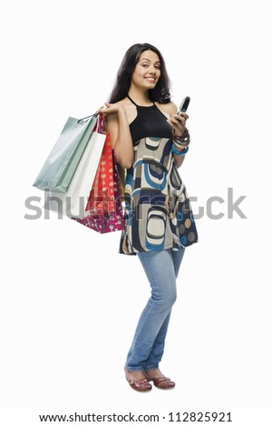 Portrait of a young woman holding shopping bags and a mobile phone - stock photo