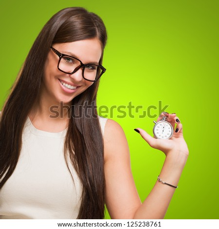Portrait Of A Young Woman Holding Stopwatch And Wearing Specs against a green background - stock photo