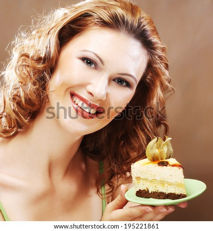 Portrait of a young woman holding up a delicious piece of cake - stock photo