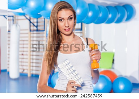 Portrait of a young woman holding weight (dumbbell) and vitamins - stock photo
