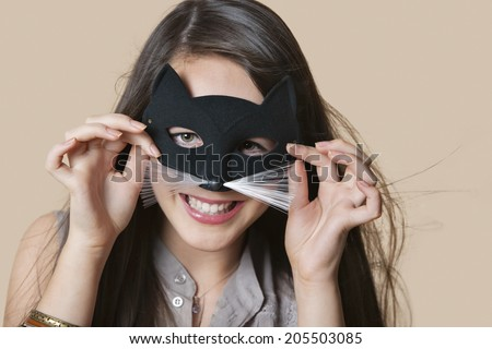 Portrait of a young woman imitating as cat while looking through eye mask over colored background - stock photo