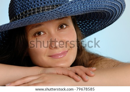Portrait of a young woman in a blue sunhat with daydreaming romantic expression - stock photo