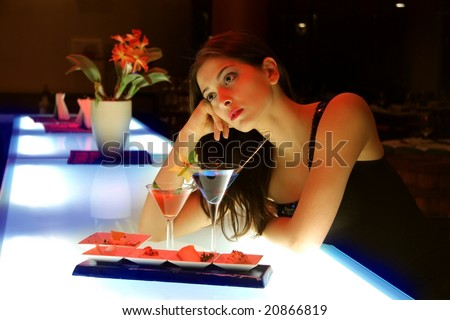 portrait of a young woman in a cocktail bar - stock photo