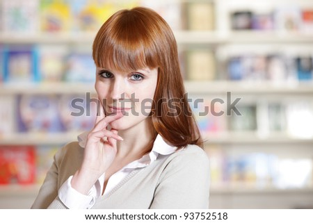 portrait of a  young woman in a library - stock photo
