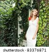 portrait of a young woman in a white dress outdoors - stock photo