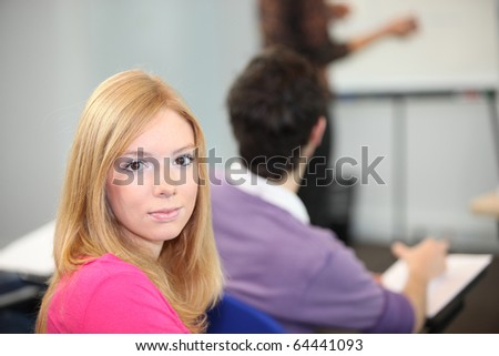 Portrait of a young woman in classroom - stock photo