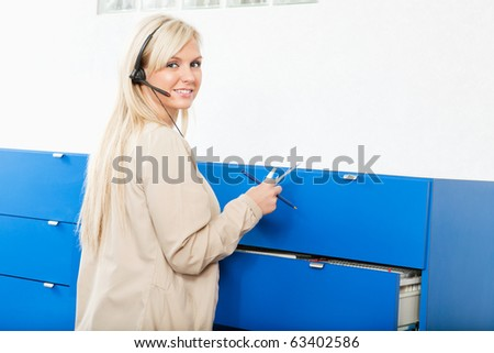Portrait of a young woman in front of wall drawers with documents - stock photo