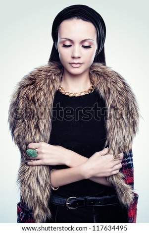 Portrait of a young woman in furs and jewels - stock photo