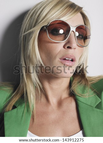 Portrait of a young woman in glasses and green jacket against white background - stock photo