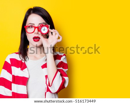 Portrait of a young woman in glasses with retro alarm clock on yellow background