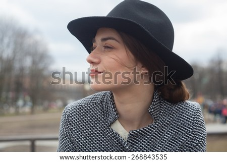 Portrait of a young woman in hat outdoors