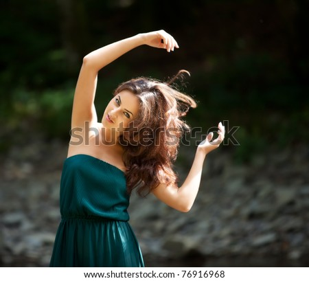 Portrait of a young woman in motion with arms raised against a dark background - stock photo