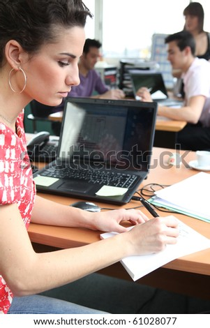 Portrait of a young woman in office - stock photo