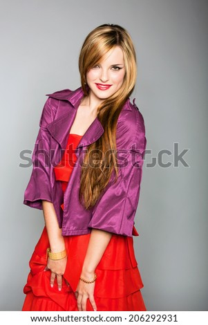 Portrait of a young woman in red dress and purple jacket. Wearing long hair loose and antique jewellery over grey studio background - stock photo