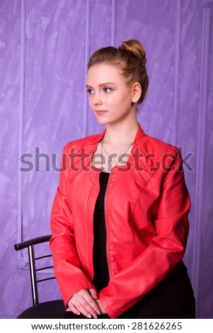 Portrait of a young woman in red jacket on a purple background - stock photo