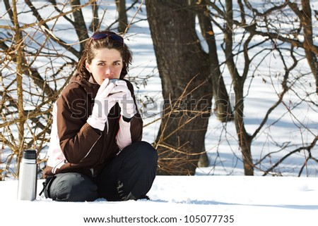 Portrait of a young woman in snowy winter forest, wearing sporty winter clothes, holding the cup of thermos bottle with some hot drink, smiling into camera - stock photo