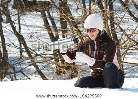 Portrait of a young woman in snowy winter forest, wearing sporty winter clothes, pouring hot tea out of a thermos bottle - stock photo