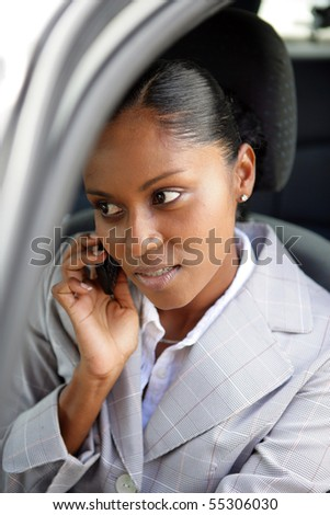 Portrait of a young woman in suit phoning in a car