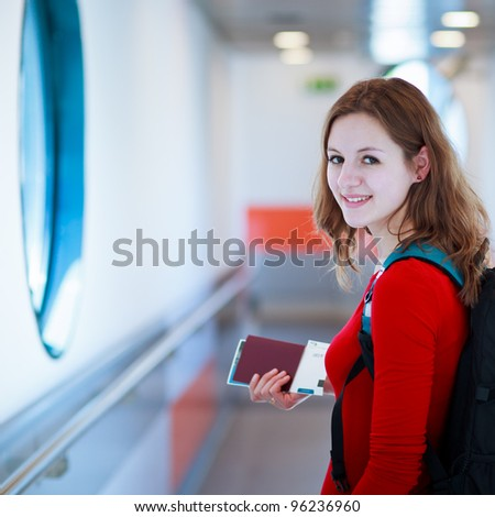 Portrait of a young woman in the boarding bridge, boarding an aircraft - stock photo