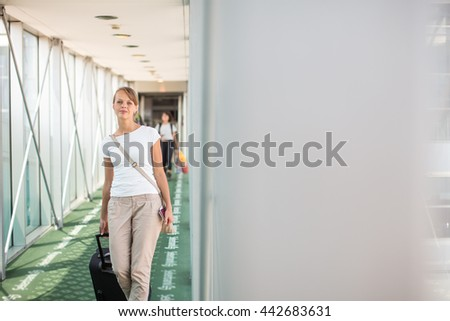Portrait of a young woman in the boarding bridge, boarding an aircraft (color toned image; shallow DOF) - stock photo
