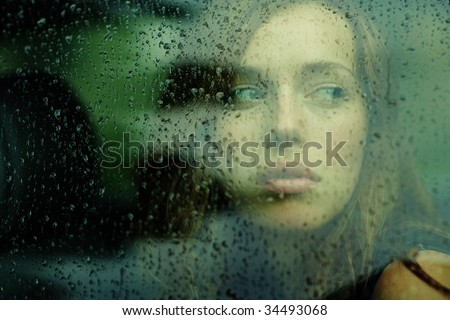 portrait of a young woman in the car during the rain - stock photo