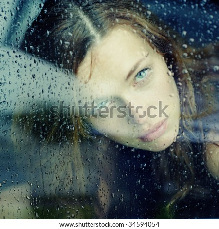 portrait of a young woman in the car during the rain