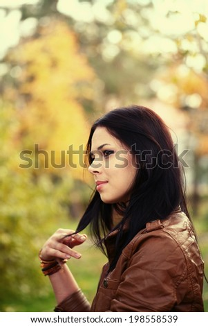 Portrait of a young woman in the park in profile - stock photo