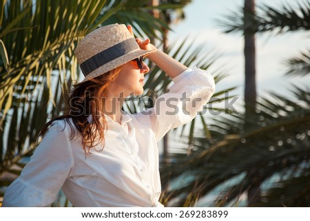 Portrait of a young woman in the straw hat, tropical background - stock photo