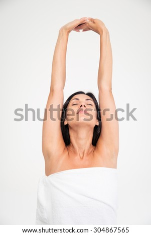 Portrait of a young woman in towel stretching hands isolated on a white background