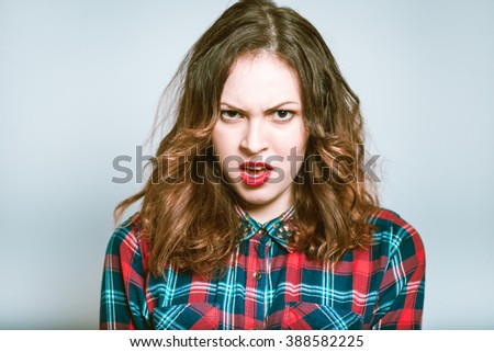 Portrait of a young woman irritated isolated on a gray background - stock photo