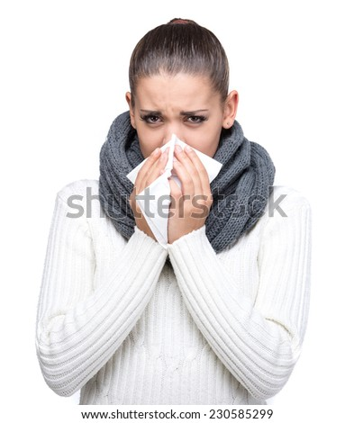 Portrait of a young woman is blowing nose, isolated on white background. - stock photo