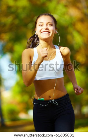 portrait of a young woman jogging and listening to the player - stock photo