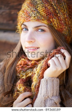 Portrait of a young woman leaned to a wooden wall in autumn outdoor. - stock photo