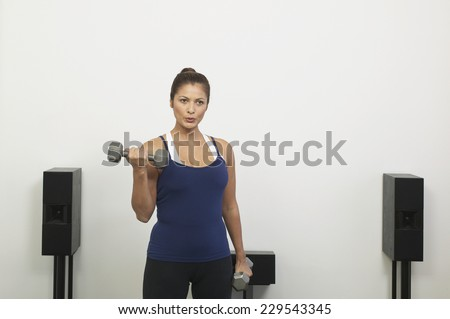 Portrait of a young woman lifting two dumbbells
