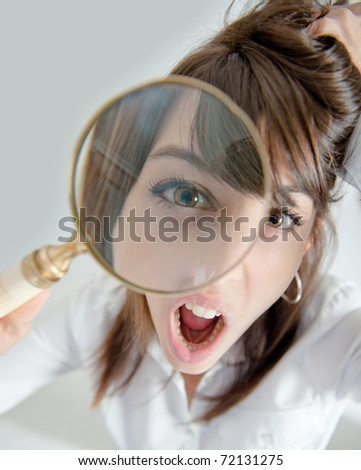 Portrait of a young woman looking at the camera through a magnifying glass with an outraged expression - stock photo