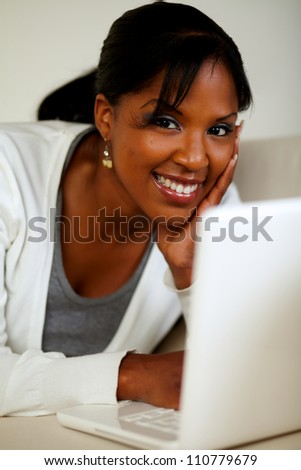 Portrait of a young woman looking at you in front of her laptop while lying on sofa