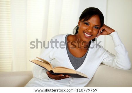 Portrait of a young woman looking at you while holding a book at home indoor - stock photo