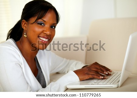 Portrait of a young woman looking at you while working on laptop at home indoor - stock photo